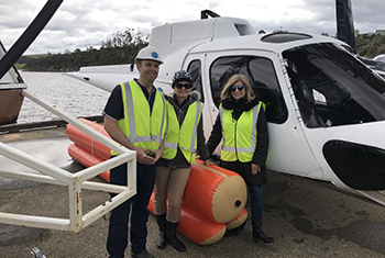 Sheryl Frame and 2 colleagues standing next to a helicopter.
