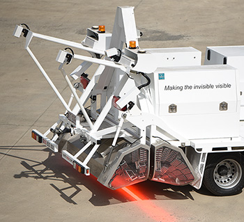 Truck with contraption on back that is projecting a bright beam of light on the ground.