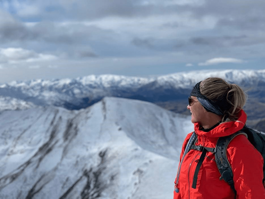 Person looking over snow covered moutain tops.
