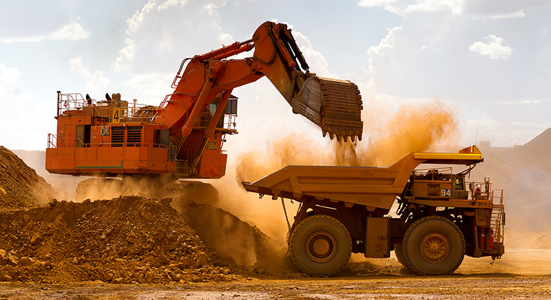 Large excatvator dumping rocks and dirt into the back of a dump truck.