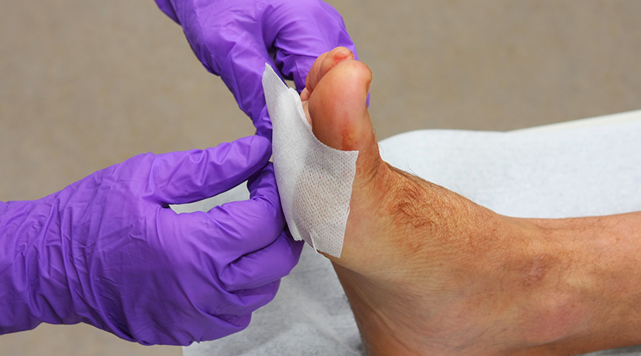Doctor applying bandage to patients foot