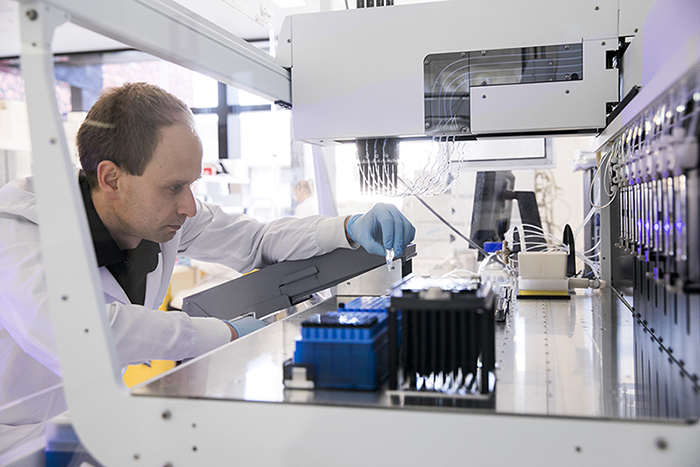 Researcher setting up experiment in complex machine