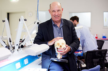 Man holding model of a skull in a science lab.