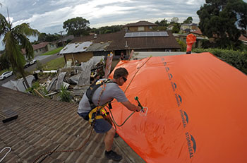 Person on roof attaching a large platic sheet to a roof using a hand tool.