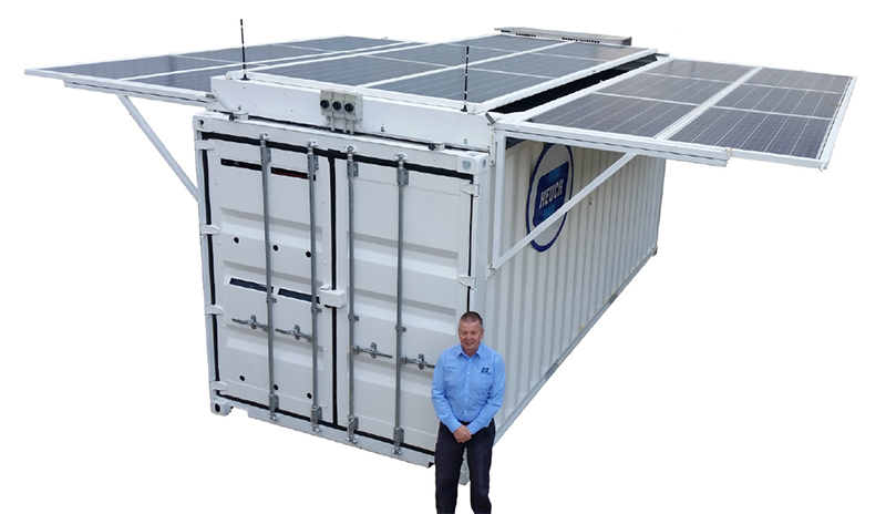Person standing in front of a white shipping container with solar panels on the top.