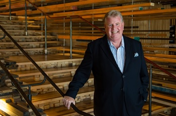 Man standing in front of Canberra's Nishi building wooden staircase.