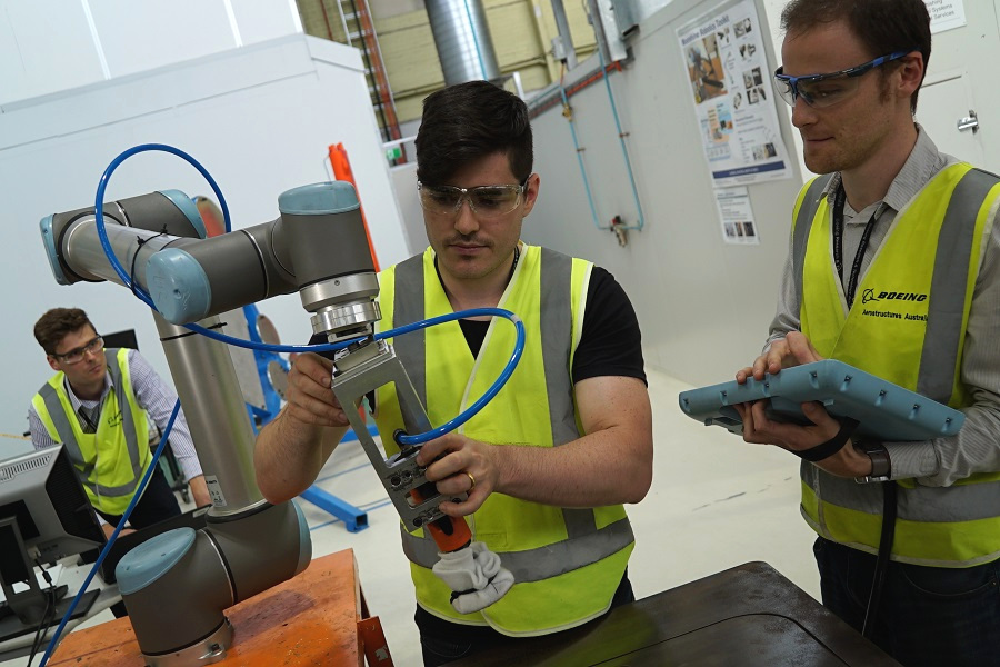 2 people adjusting a robotic in an advanced manufacturing facility
